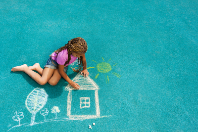 little girl drawing house sun and trees with chalk on playground